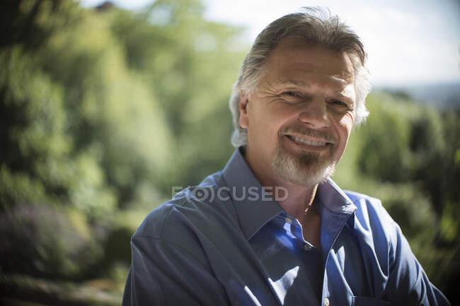 Portrait homme âgé confiant sur terrasse ensoleillée — Photo de stock