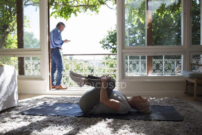 Старша жінка розтягується на йога мат на літньому балконі двері балкону — стокове фото