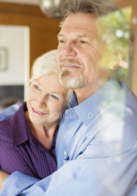 Тихая старшая пара обнимается у окна — стоковое фото