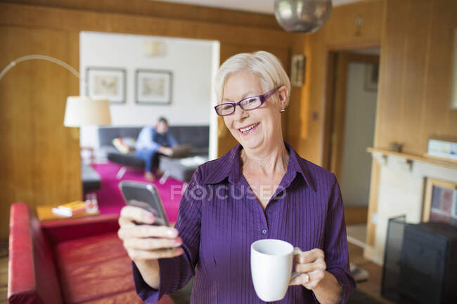 Happy senior woman using smart phone and drinking tea in living room — Stock Photo