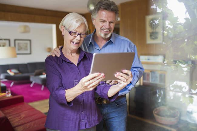 Glückliches Senioren-Paar nutzt digitales Tablet im Wohnzimmer — Stockfoto
