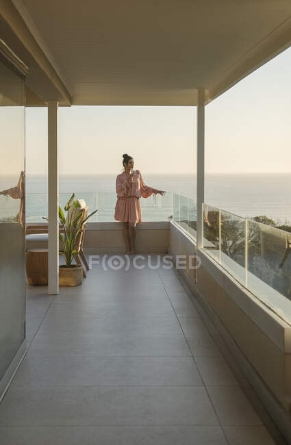 Woman relaxing with white wine on luxury balcony with ocean view — Foto stock