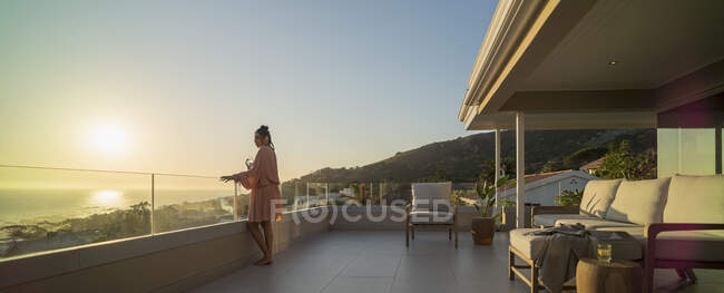 Woman with white wine enjoying sunset ocean view on luxury balcony — Foto stock