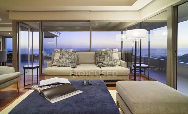 Главная витрина интерьер гостиной с видом на океан в сумерках — стоковое фото