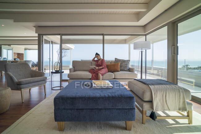 Donna rilassante con tablet digitale sul divano di casa vetrina soggiorno — Foto stock