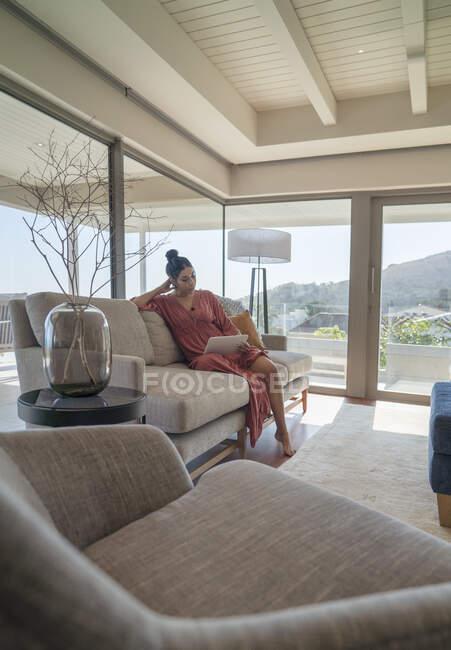 Женщина расслабляется с цифровой планшет на диване в роскошной гостиной — стоковое фото