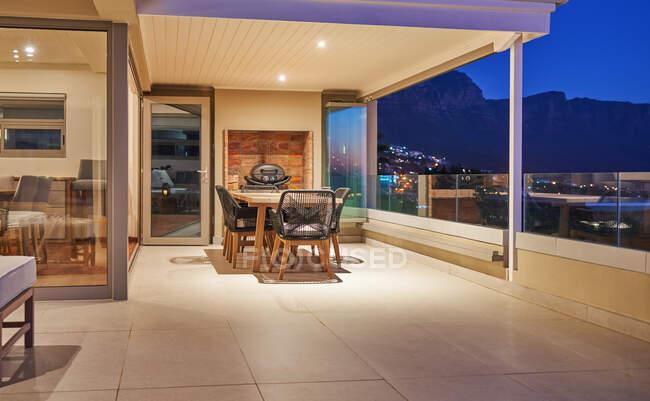 Tavolo da pranzo sul patio vetrina casa di lusso di notte — Foto stock