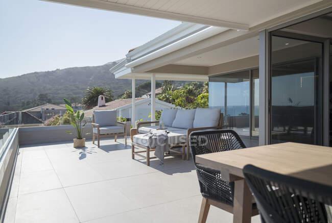 Tavolo da pranzo e divano sul patio vetrina casa soleggiata — Foto stock