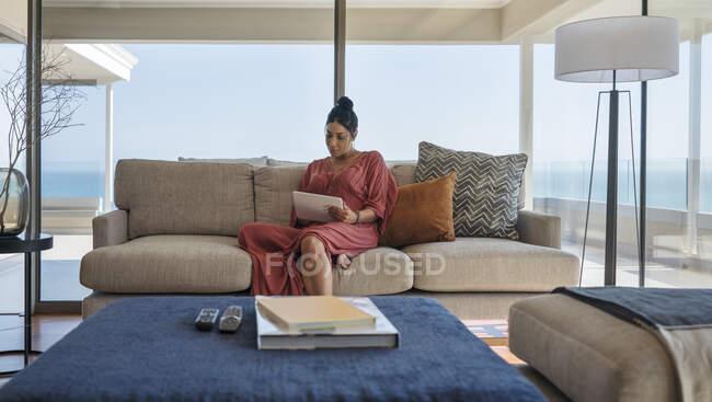 Женщина расслабляется с цифровой планшет на роскошный дом витрина диван — стоковое фото