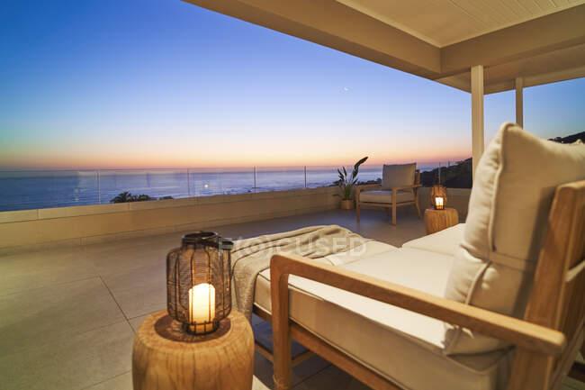 Lanterna e poltrona su un patio di lusso con vista panoramica sull'oceano al tramonto — Foto stock
