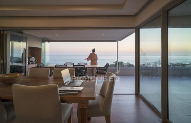Donna rilassante sul balcone di lusso con vista sull'oceano tramonto — Foto stock