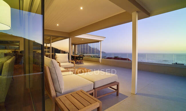 Chaise lounge sul patio di lusso con vista sul tramonto sull'oceano — Foto stock