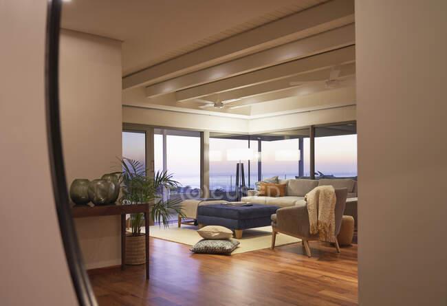 На заході сонця відбивається розкішний вітальня з видом на океан. — стокове фото
