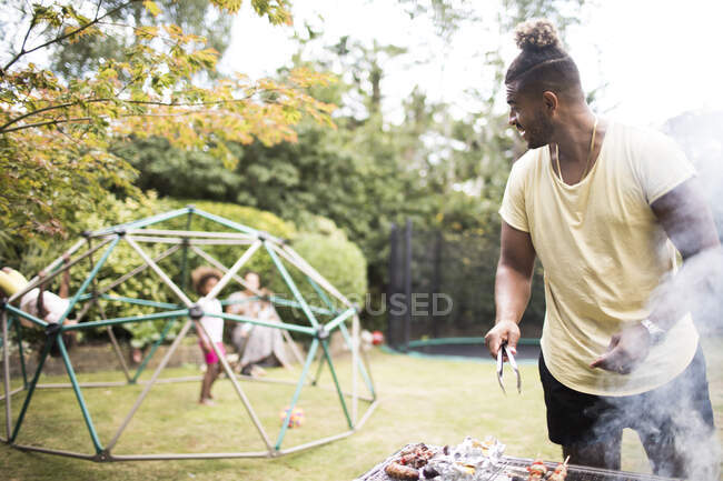 Father barbecuing at grill and watching kids play in summer backyard — Stock Photo