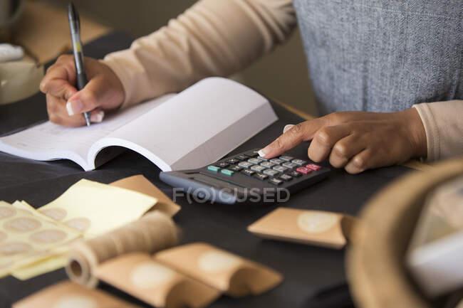 Feche o proprietário da loja com a calculadora preenchendo o livro — Fotografia de Stock