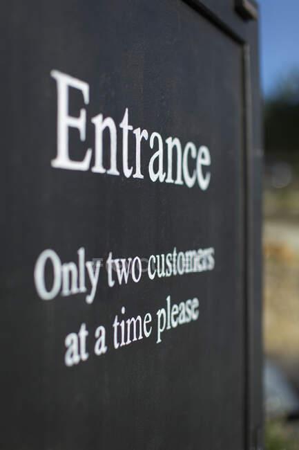 Sinal de distanciamento social na entrada da loja — Fotografia de Stock