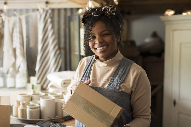 Retrato dono da loja feminina feliz com pacote — Fotografia de Stock