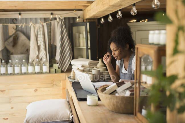 Жіночий власник магазину працює на ноутбуці за прилавком. — стокове фото