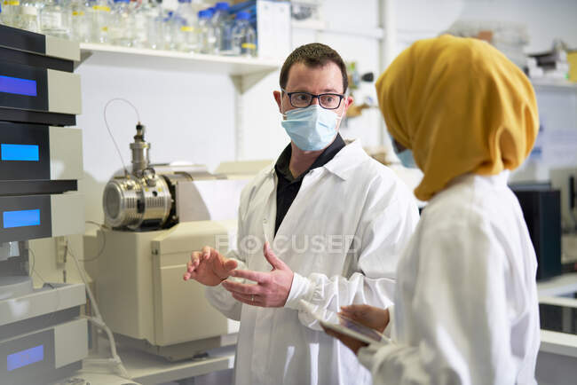 Des scientifiques masqués parlent en laboratoire — Photo de stock