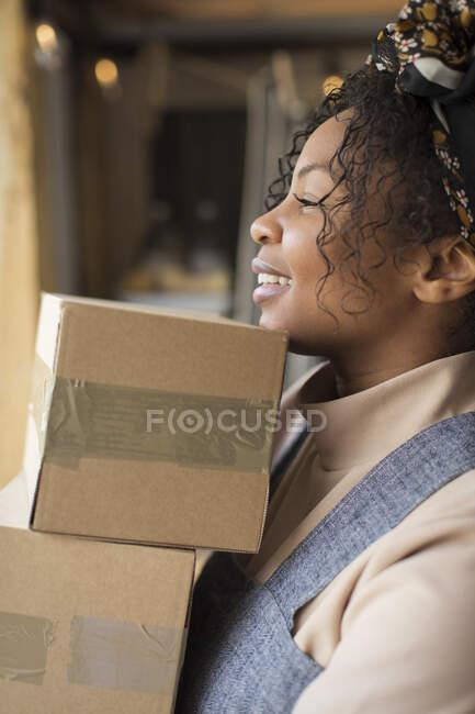 Mulher feliz loja proprietário transportando pilha de caixas — Fotografia de Stock