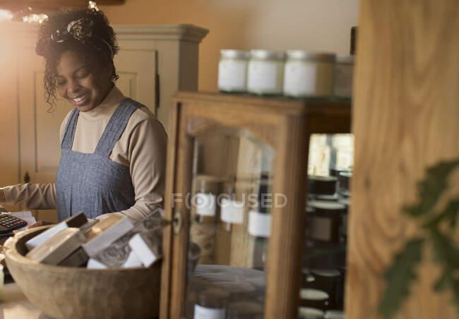 Посмішка власник магазину, який працює за прилавком. — стокове фото