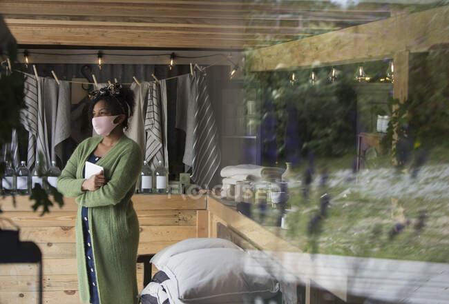 Pensativo dono da loja feminina em máscara facial olhando para longe — Fotografia de Stock