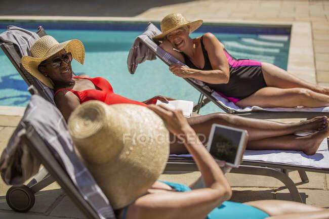 Felices amigas mayores en vacaciones tomando el sol en la piscina soleada - foto de stock