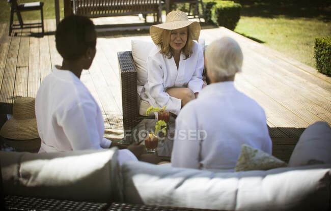 Senior women friends talking on summer patio — Stock Photo