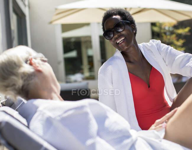 Happy senior women friends sunbathing on spa patio — Stock Photo