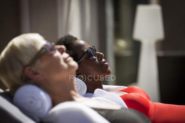 Serene senior women friends sunbathing in sunglasses on sunny patio — Stock Photo