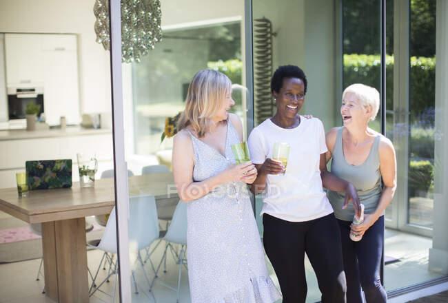 Felice anziane amiche che bevono e ridono sul patio soleggiato — Foto stock