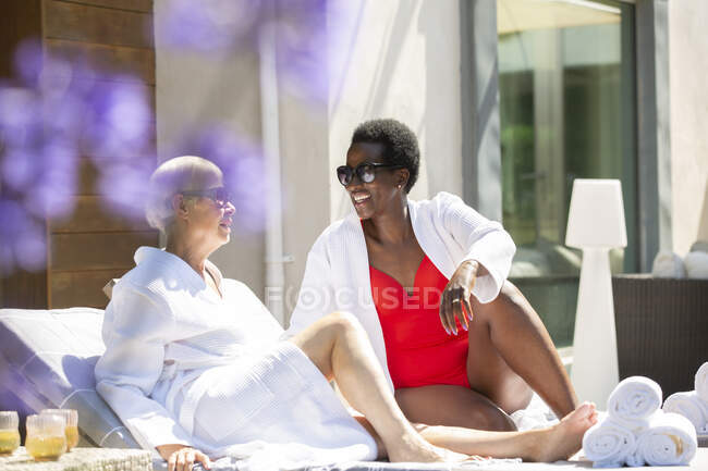Senior women friends relaxing on sunny summer hotel patio — Stock Photo