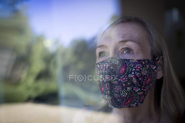 Mujer mayor preocupada en mascarilla en la ventana - foto de stock