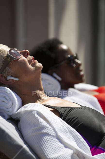 Senior woman with earbud headphones sunbathing on sunny patio — Stock Photo