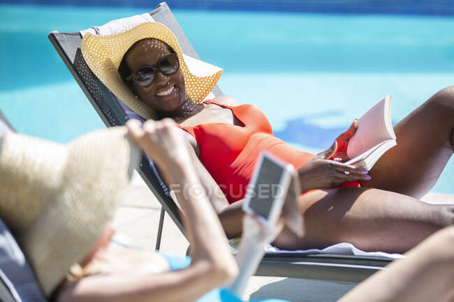 Happy senior women friends relaxing and sunbathing at sunny poolside — Stock Photo