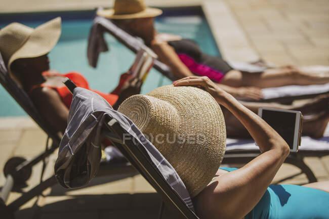 Senior women friends sunbathing at sunny summer poolside — Stock Photo