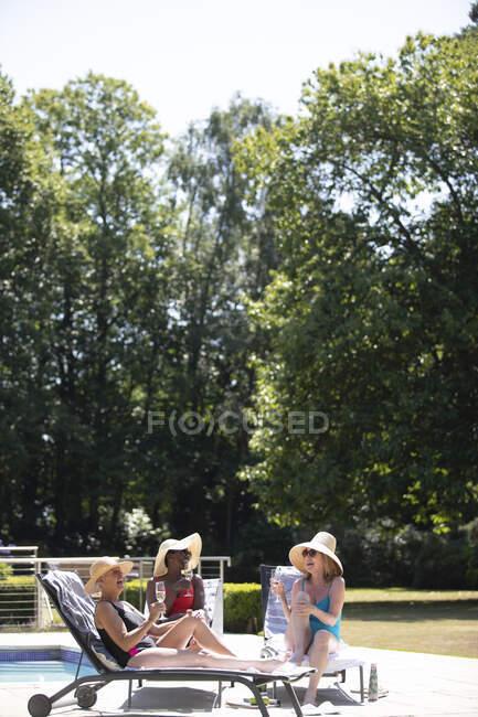 Senior women friends sunbathing drinking champagne at sunny poolside — Stock Photo