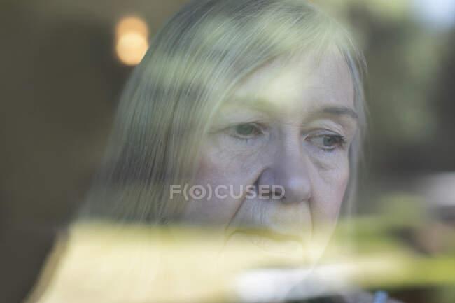 De cerca mujer mayor preocupada en la ventana - foto de stock