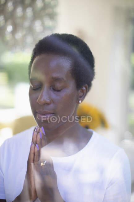 Mujer madura serena meditando en la ventana con las manos apretadas - foto de stock