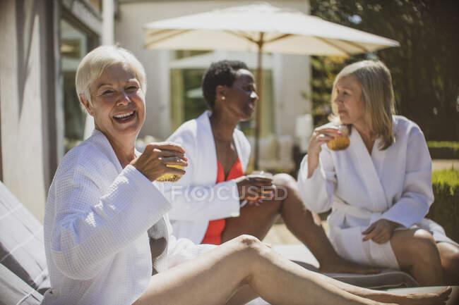 Portrait happy senior women friends relaxing on sunny hotel patio — Stock Photo