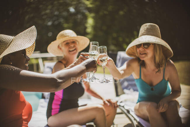 Senior women friends drinking champagne at summer poolside — Stock Photo