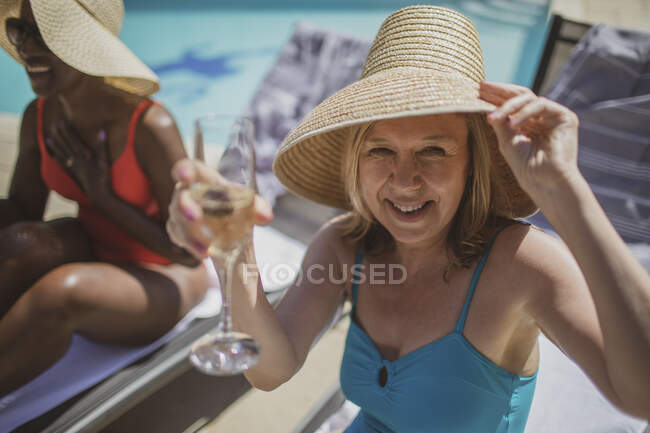 Portrait happy senior woman drinking champagne at sunny poolside — Stock Photo