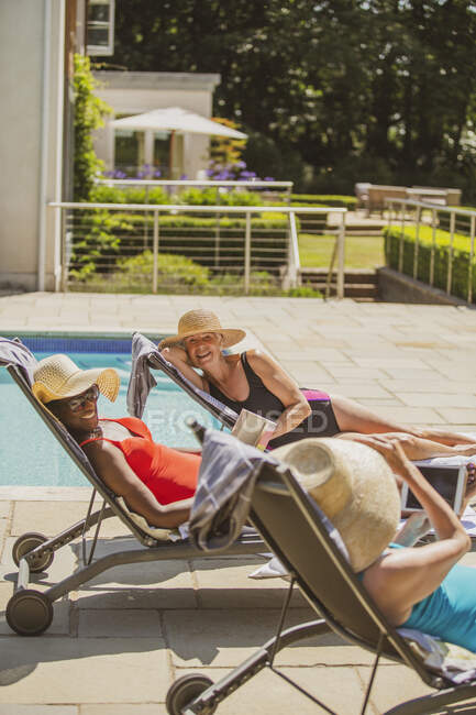 Happy senior women friends sunbathing at sunny summer poolside — Stock Photo
