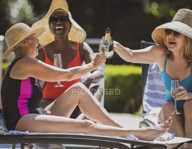 Happy senior women friends drinking champagne on sunny summer patio — Stock Photo