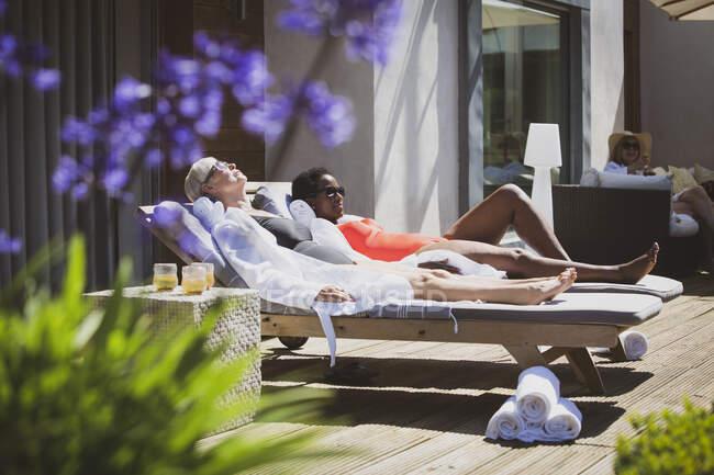 Senior women friends sunbathing on sunny summer hotel patio — Stock Photo