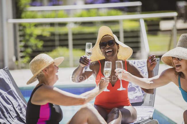 Mulheres idosas felizes amigos bebendo champanhe na ensolarada piscina de verão — Fotografia de Stock