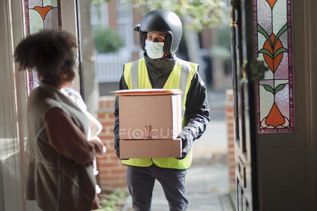 Mulher recebendo pacotes de homem de entrega na máscara facial na porta da frente — Fotografia de Stock