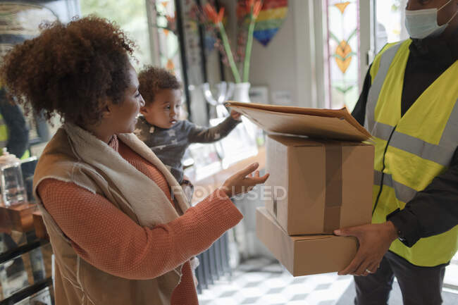 Mother and baby daughter receiving packages from delivery person — Stock Photo