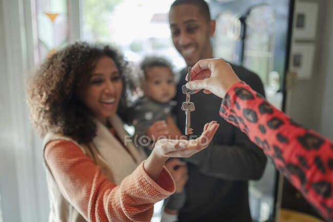 Happy family receiving new house keys from realtor — Stock Photo