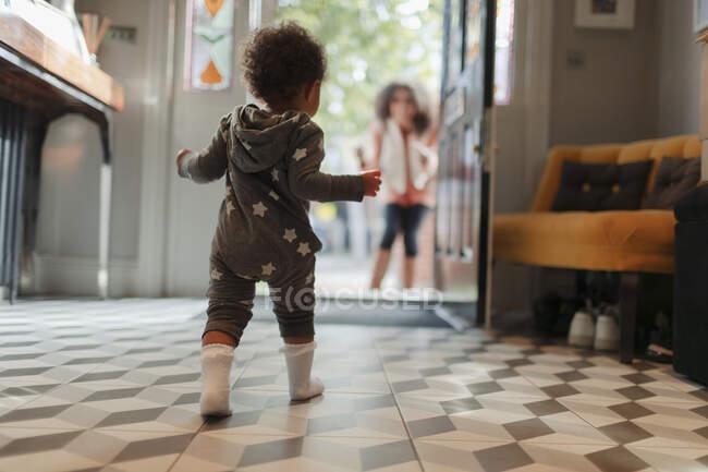 Linda niña en pijama de estrella caminando a la madre en la puerta abierta - foto de stock